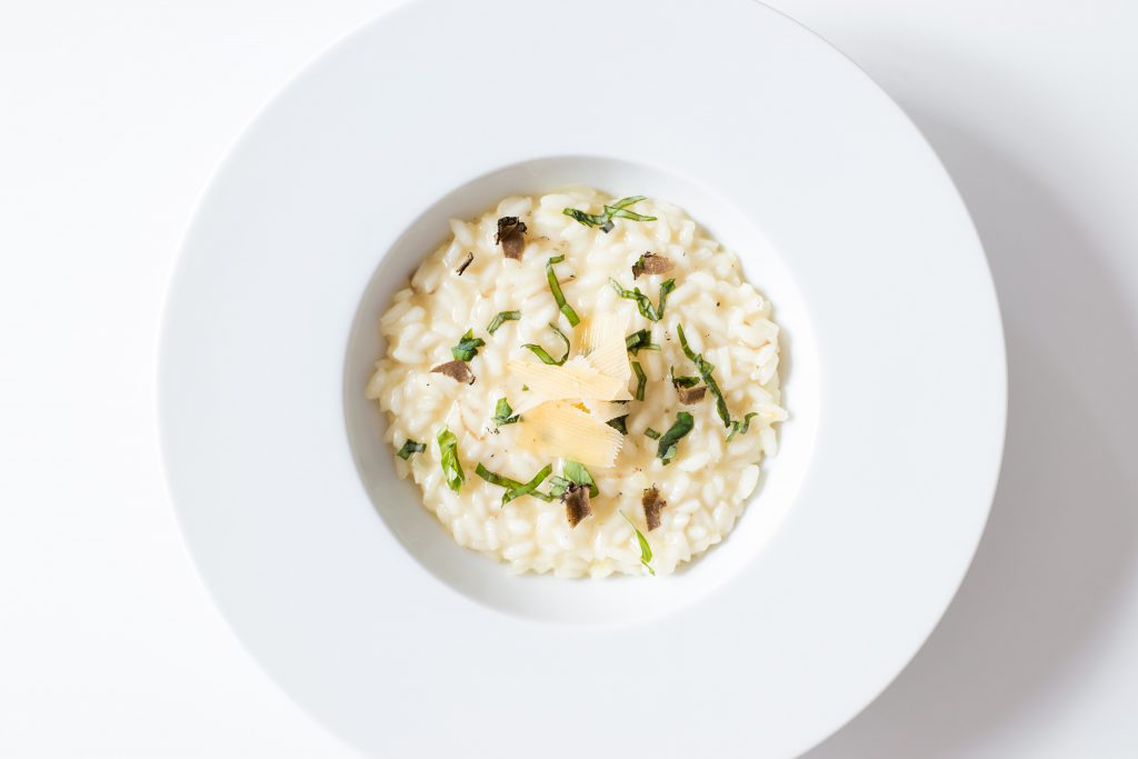 Risotto op een groot wit bord met kaas